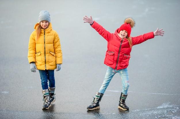 Schattige kleine meisjes die op de ijsbaan schaatsen Premium Foto