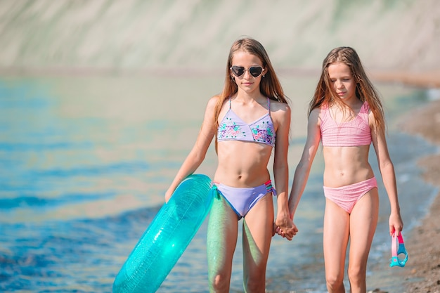 Schattige kleine meisjes die plezier hebben op het strand Premium Foto