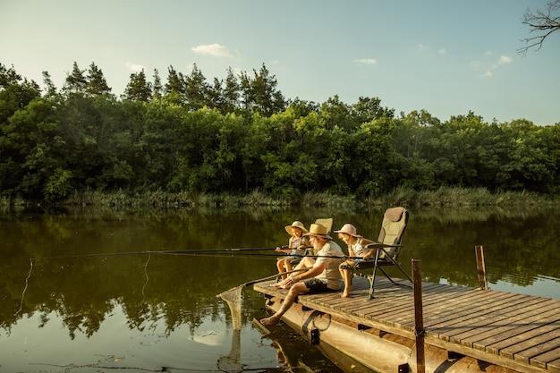 Schattige kleine meisjes en hun opa zijn aan het vissen in het meer of de rivier Gratis Foto