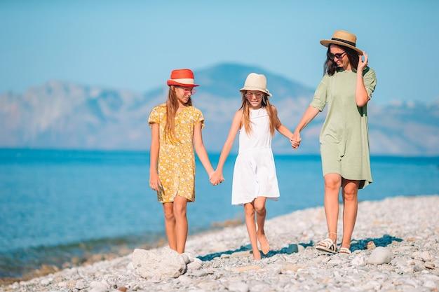 Schattige kleine meisjes en jonge moeder op tropisch wit strand Premium Foto