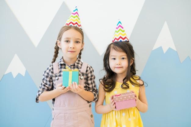 Schattige kleine meisjes in kleurrijke feestmutsen Premium Foto