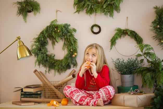 Schattige kleine vrouw in pyjama's voor kerstpijama Premium Foto