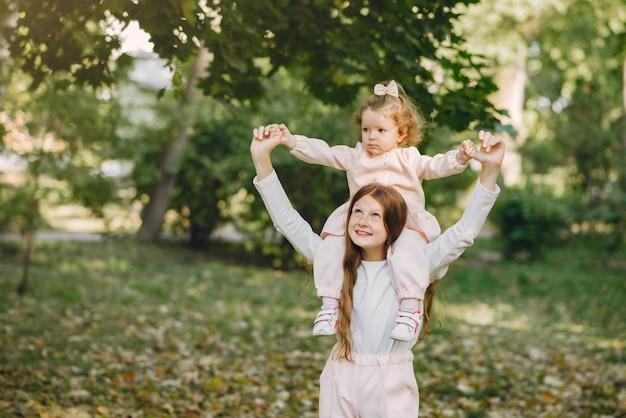Schattige kleine zusjes spelen in een voorjaar park Gratis Foto
