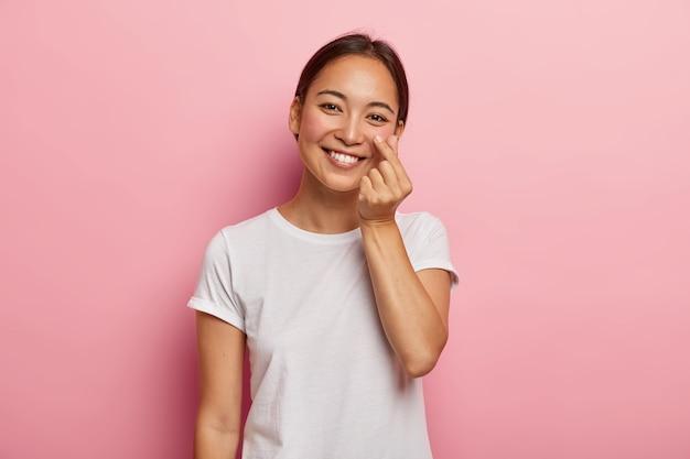 Schattige lachende vrouw raakt rode huid op wangen met vinger, toont de zachtheid ervan, geeft om haar schoonheid, kantelt het hoofd, glimlacht zachtjes, gekleed in een casual wit t-shirt, modellen binnen Gratis Foto