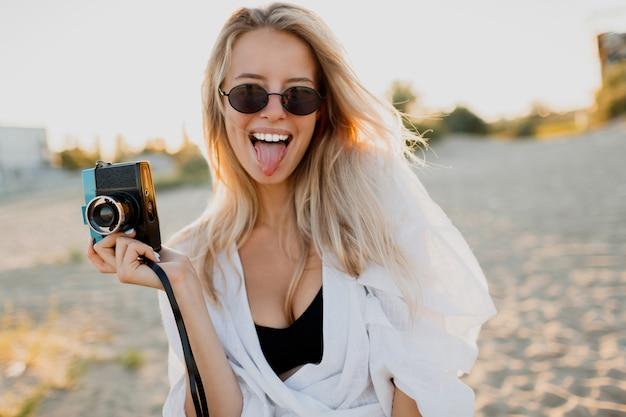 Schattige meid met retro camera grimassen maken en poseren op het strand in de buurt van de oceaan. zomervakantie. prachtig zonlicht. Gratis Foto