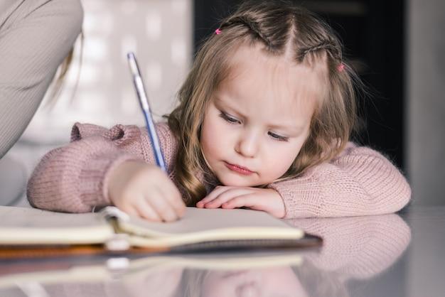 Schattige peuter meisje tekenen met pen aan tafel Gratis Foto