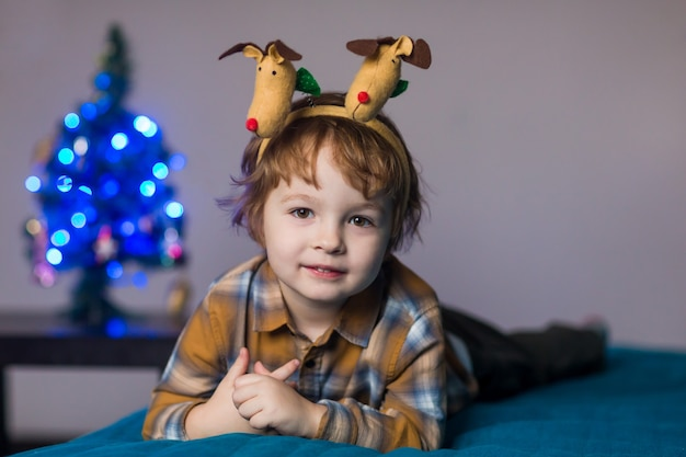 Schattige schattige jongen met hoorns van een hert op zijn hoofd viert het nieuwe jaar en kerstmis Premium Foto