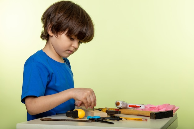 Schattige schattige jongen werken met tools in blauw t-shirt en wit Gratis Foto