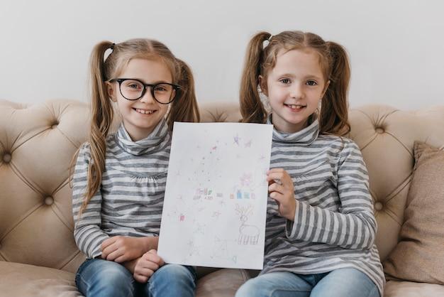 Schattige tweeling met een tekening Gratis Foto