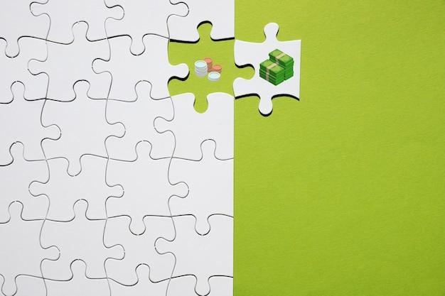 Scheiding van munt en bankbiljet op puzzel op groene achtergrond Gratis Foto