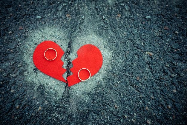 Scheidingsconcept - gebroken hart met trouwringen op gebarsten asfalt. afgezwakt Premium Foto
