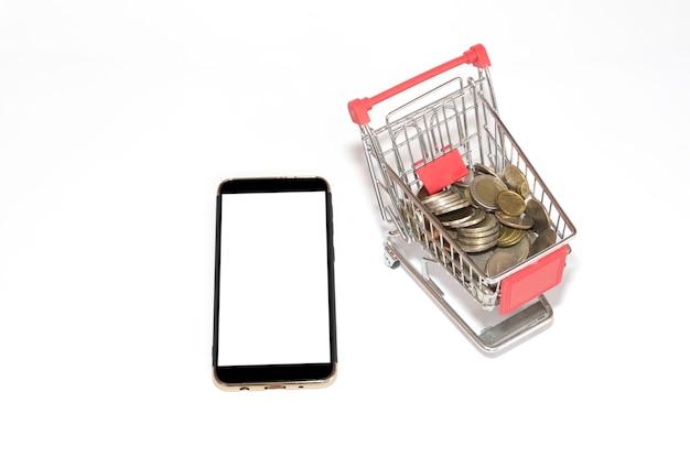 Scherm van de mobiele telefoon met munten in het kleine winkelwagentje Premium Foto