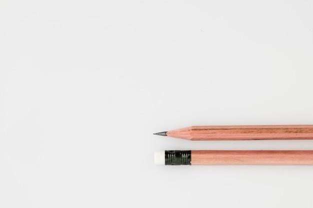Scherp potlood tegen de gum aan het andere uiteinde van potlood op witte achtergrond Premium Foto