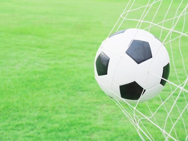 Schietend schot, voetbal in doel netto met de groene achtergrond van het grasgebied Gratis Foto