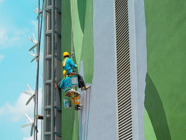 Schilders schilderen buitenkant van het gebouw Premium Foto
