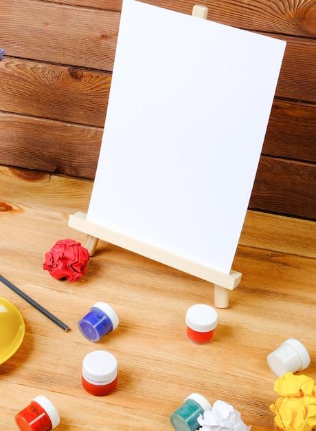 Schildersezel, kunstborstels en koffie op een houten tafel. werkplek van de kunstenaar. creativiteit en hobby concept. Premium Foto
