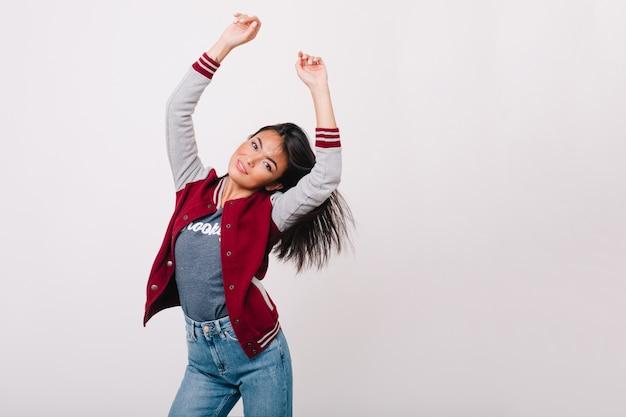Schitterend aziatisch meisje met licht gebruinde huid gelukkig dansen in lichte kamer. aanbiddelijk vrouwelijk model in spijkerbroek met sluik zwart haar dat pret heeft voor witte muur. Gratis Foto