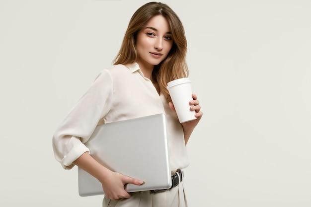 Schitterend donkerbruin model in witte kleren met laptop en koffie Premium Foto