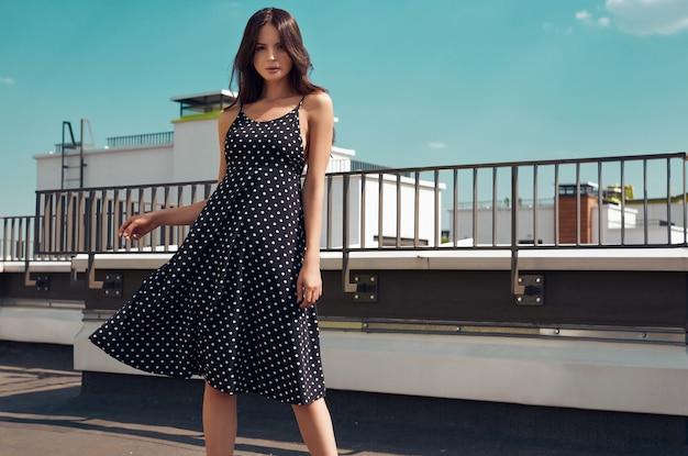 Schitterend helder brunette in manierkleding het stellen op het dak van een gebouw Premium Foto