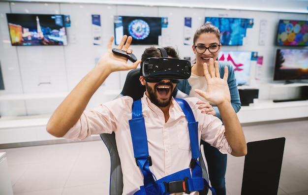 Schitterend jeugdig hipsterpaar dat pret heeft terwijl het controleren van vr in de technologieopslag. Premium Foto