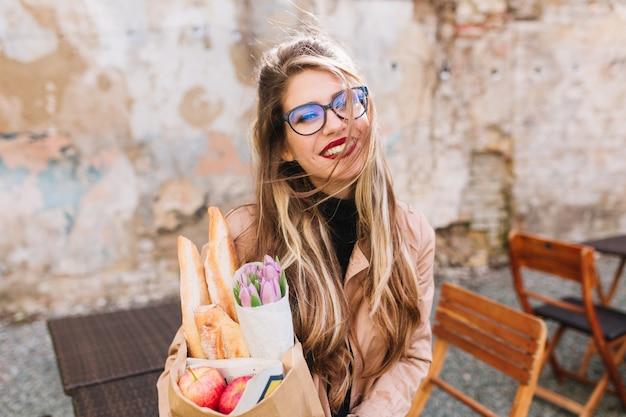 Schitterend meisje na fotosessie vers eten gekocht en koffie drinken genieten van een zonnige dag. stijlvolle jonge vrouwelijke fotograaf boodschappentas en kopje cappuccino poseren op het terras te houden. Gratis Foto