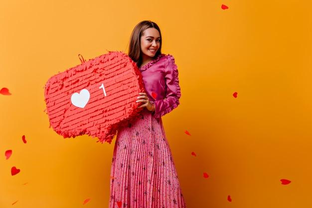 Schitterend, vrolijk, vrolijk meisje poseren met rode versieringen in haar handen. portret van bruinharige vrouw in roze outfit tegen muur van confetti in vorm van harten Gratis Foto