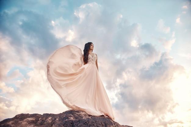 Schitterend vrouwenbrunette in de bergen bij zonsondergang en blauwe hemel met wolken Premium Foto