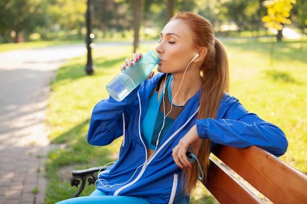 Schitterende atletische vrouw die in het park in de ochtend uitwerkt Premium Foto