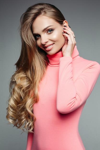 Schitterende blondevrouw in roze sweater met golvend volumed haar. Premium Foto