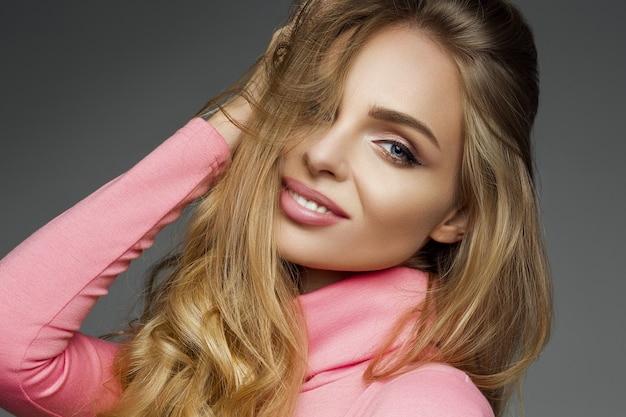 Schitterende blondevrouwensualiteit die bij camera glimlachen. Premium Foto
