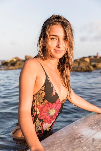 Schitterende dame die zich dichtbij surfplank in overzees bevindt Gratis Foto