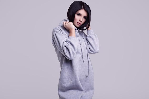 Schitterende donkerbruine vrouw in manier blauwe hoodie in studio Premium Foto