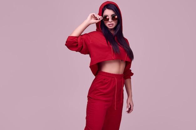 Schitterende donkerbruine vrouw in manier rode hoodie in studio Premium Foto