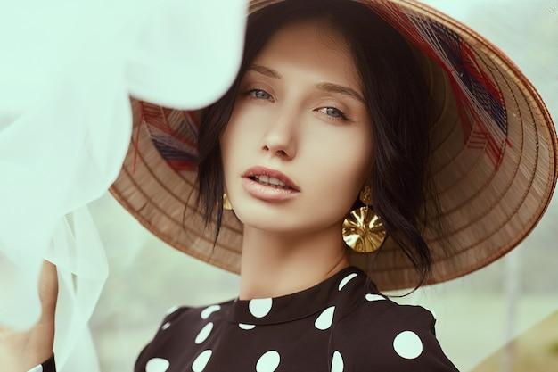 Schitterende donkerbruine vrouw in manierkleding met stro chinese hoed Premium Foto
