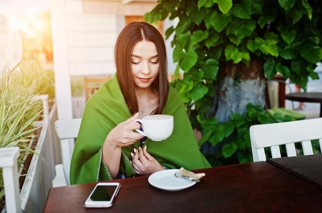 Schitterende donkerbruine vrouwenzitting op de lijst in de plaid van de koffiedekking met kop van koffie. Premium Foto