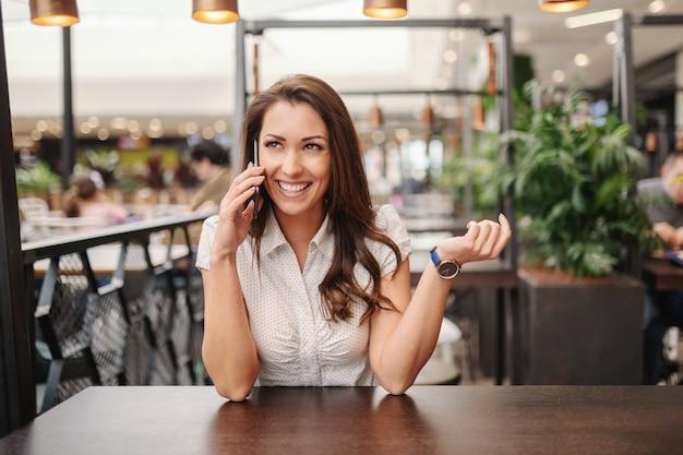 Schitterende glimlachende kaukasische donkerbruine zitting bij koffiewinkel en het spreken op de slimme telefoon. Premium Foto