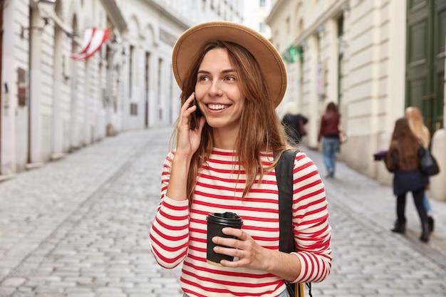 Schitterende glimlachende toerist slentert door de stad, voert een telefoongesprek, houdt koffie voor afhaalmaaltijden, geconcentreerd ergens in de verte Gratis Foto