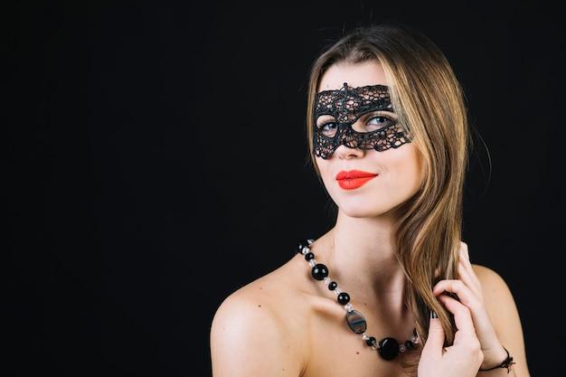 Schitterende glimlachende vrouw in maskerade carnaval masker op zwarte achtergrond Gratis Foto
