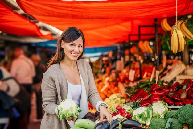 Schitterende jonge vrouw bij landbouwersmarkt. verse bloemkool vasthouden. Premium Foto