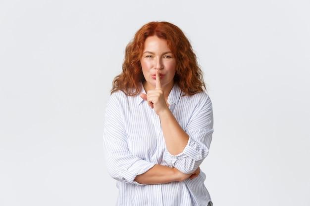 Schitterende roodharige vrouw van middelbare leeftijd vraagt stil te houden Premium Foto