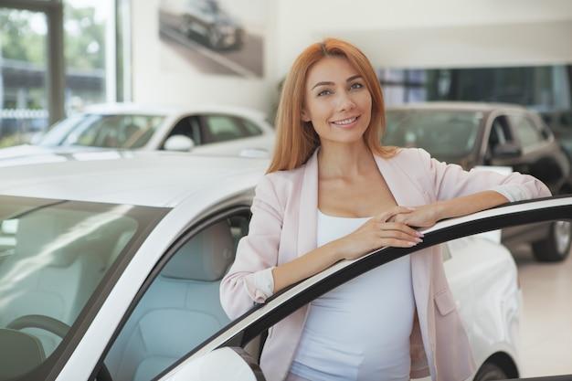 Schitterende vrouw die een nieuwe auto kiest bij het handel drijven Premium Foto