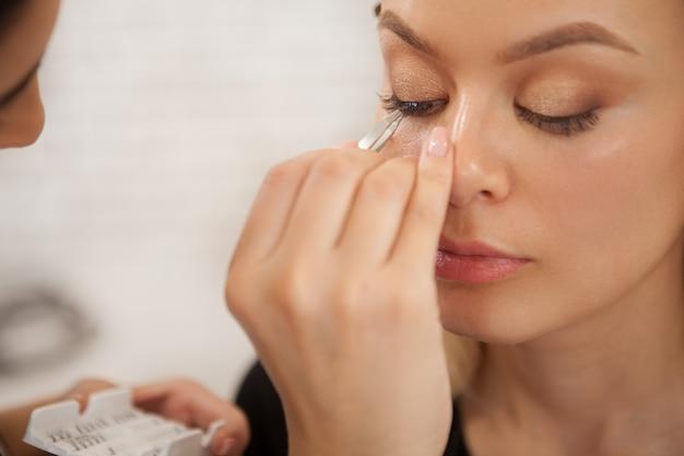 Schitterende vrouw die professionele make-up krijgt Premium Foto