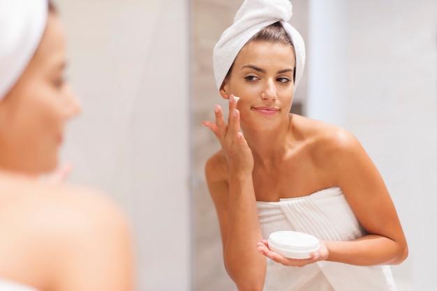 Schitterende vrouw die vochtinbrengende crème op gezicht toepast Gratis Foto