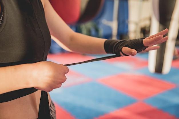 Schitterende vrouw, mma vechter in gymnastiek tijdens opleiding. voorbereiding op een wedstrijd met harde kooien Premium Foto