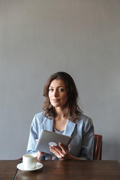 Schitterende vrouwenzitting die binnen tabletcomputer met behulp van. Gratis Foto