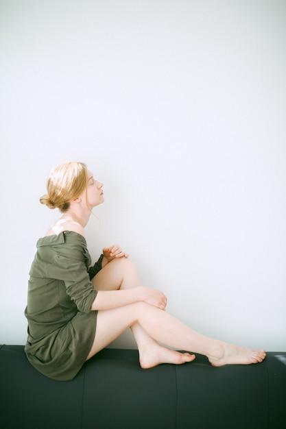 Schitterende vrouwenzitting en het denken met haar ogen sloot in ruimte met witte achtergrond in groene kleding. Gratis Foto