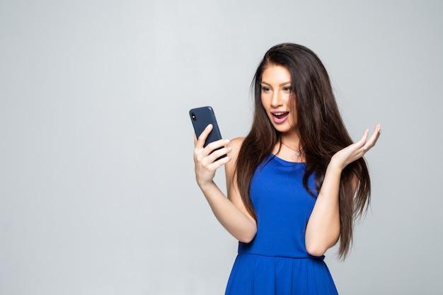 Schokkend nieuws. zaken en technologie. sluit omhoog portret van verraste jonge vrouw gebruikend slimme geïsoleerde telefoon Gratis Foto