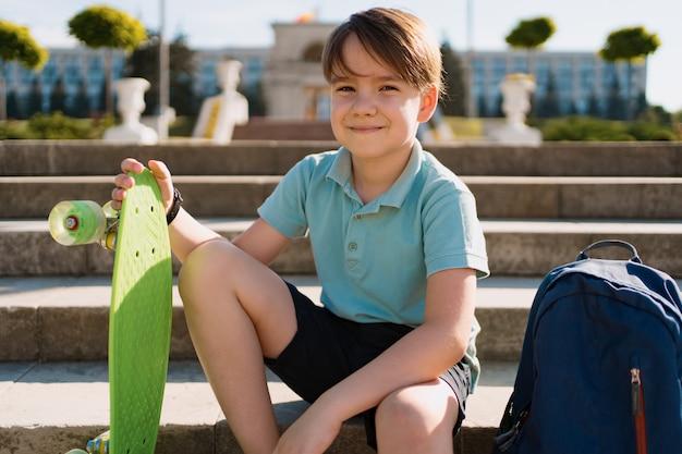 School jongen in blauw poloshirt zittend op de trap met een blauwe rugzak en groene cent board Gratis Foto