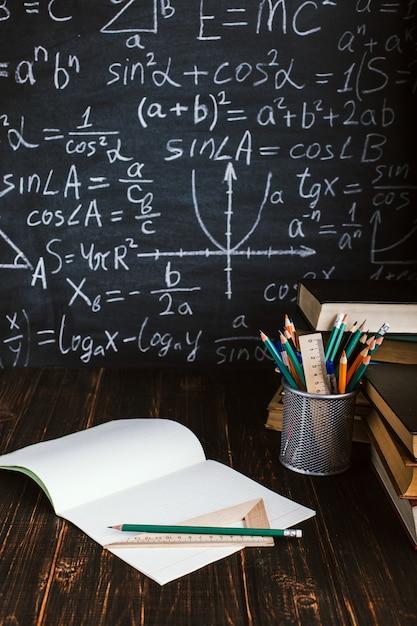 Schoolbank in de klas, met boeken op de achtergrond van krijt bord met schriftelijke formules Premium Foto