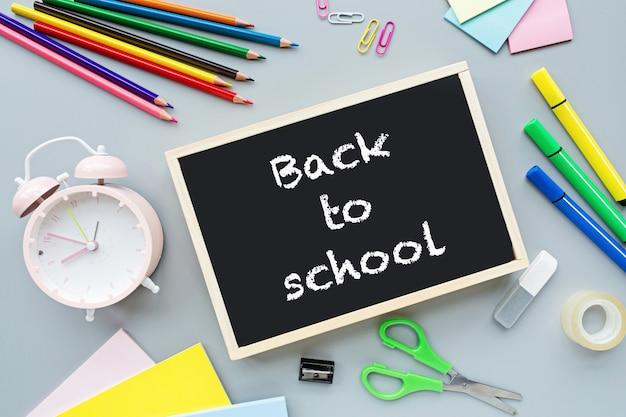 Schoolbenodigdheden briefpapier, kleurpotloden, clips, wekker, papier op grijs Premium Foto